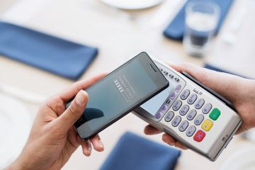 Paying with smartphone in restaurant --- Image by © Tomas Rodriguez/Corbis